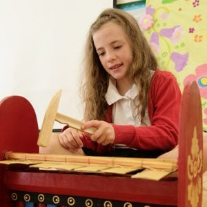 This is an action shot of a Primary School girl playing one of the Budget Gamelan 7 Key Large instruments.