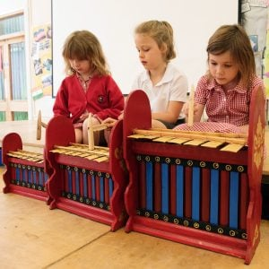 This is an action shot of three Primary School girls playing on the three sizes of Budget Gamelan 7 key instruments.