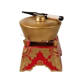This is a product image of the Bonang - 1 Pan - Premium - Medium. It is a gold coloured pan with a gold boss on the top suspended by wire on a wooden frame. The frame is red with gold detail. There is a wooden beater that is wrapped in string at one end laying on the pan. The image has been taken from a head on position.