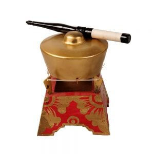 This is a product image of the Bonang - 1 Pan - Premium - Small. It is a gold coloured pan with a gold boss on the top suspended by wire on a wooden frame. The frame is red with gold detail. There is a wooden beater that is wrapped in string at one end laying on the pan. The image has been taken from a head on position.