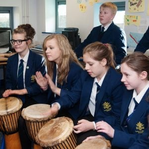This is an action shot of some Secondary Schools students playing Djembes during a music workshop.