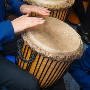 This is an action shot of a Secondary School students playing a Djembe. It is a close up image of the top half of the Djembe and the student's hands in place.