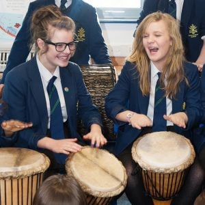 This is an action shot of two Secondary School girls playing Djembes.