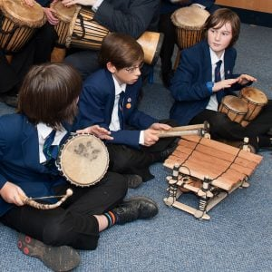 This is an action shot of some Secondary School boys playing a variety of West African instruments including a Talking Drum, a Balafon and our Bongos (African Bongos). In the background are some Djembe players.