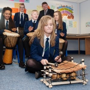 This is an action shot of a Secondary School girl playing a Balafon. Behind her are students playing Djembes.