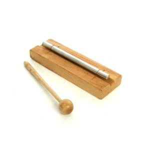 This is a product image of the Chime Bar - 1 note, stainless. It is a rectangular wooden body with a single chime bar attached. The beater is lying to the left. The instrument is angled facing from the top left to the bottom right.