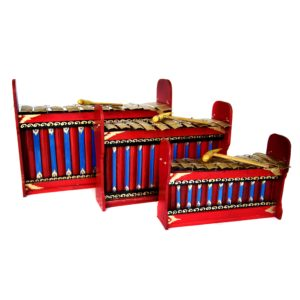 This is a product image of the Gamelan - Budget - 7 key - 3 Pack. It contains three red and blue instruments with gold keys suspended by wire, with the photo taken head on. Each instrument has a beater laying on it. The image shows the Gamelan - Budget - Small 7 key, the Gamelan - Budget - Large 7 key and the Gamelan - Budget - Medium 7 key.