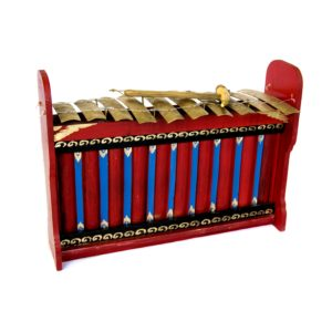 This is a product image of the Gamelan (Gangsa Kantilan) - Budget - Small 10 key. It is an angled shot with the front of the instrument facing to the right. It is red and blue with gold keys suspended by wire, and the beater is lying on top of the keys.