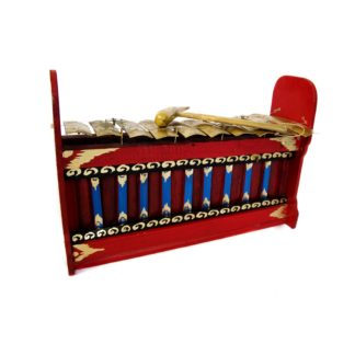 This is a product image of the Gamelan (Gangsa Pemadi) - Budget - Medium 10 key. The image has been taken from the front and the instrument is facing slightly to the right. It is red and blue with gold keys suspended by wire, and the beater is lying on top of the keys.