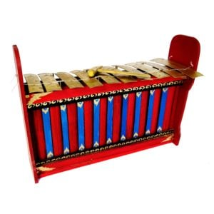 This is a product image of the Gamelan (Gangsa Ugal) - Budget - Large 10 key. The image has been taken from the front and the instrument is facing slightly to the right. It is red and blue with gold keys suspended by wire, and the beater is lying on top of the keys.