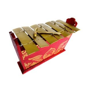 This is a product image of the Gamelan - Standard - Large - 7 key. It is red, with gold detail and has gold keys suspended from wire with a beater resting upon them. The image has been taken from above and the front with the instrument angled slightly to the right.
