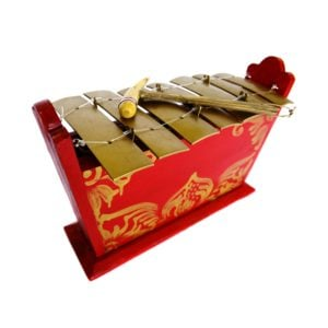 This is a product image of the Gamelan - Standard - Medium - 7 key. It is red, with gold detail and has gold keys suspended from wire with a beater resting upon them. The image has been taken from above and head on with the instrument facing to the right.