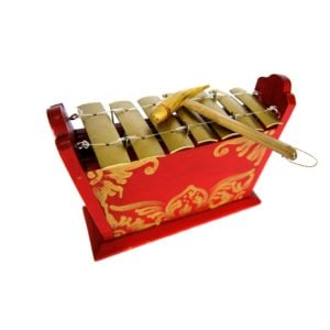 This is a product image of the Gamelan - Standard - Small - 7 key. This is a close up detail shot of the gold keys and the beater which is resting upon the instrument.