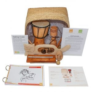 This is a product image of the Home Starter Kit - 5 Instruments. The products are packed into the Storage Basket and include one Djembe Drum - Budget - 4in diameter, 20cm high, Early Years, one Tik Tok - carved, one Egg Shaker - Medium - 7cm, Early Years, one Chime Bar - 1 note, stainless, one Animal Tambourine - Early Years. In front and to the sides are annA rydeR's Music Cards - set of 10, What It's Called + Where It's From Card and a Good Practice Guide.