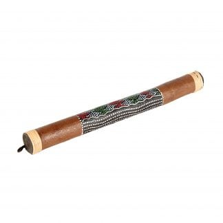 This is a product image of the Rainstick - 40cm, bamboo, painted. It is a wooden tube that has been decorated in the middle third by paint dots, closely placed together to make a consistent pattern. The instrument is laying flat and angled from bottom left to top right.