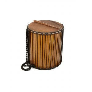 Sangban - 16in diameter, 50cm high, recycled wood. It is standing upright with one of the handles draped downwards to the left. A Dundun Beater is lying on top of the drum.