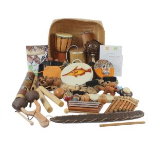 This is a product image of the World Music Basket - Large - 30 Instruments. The large array of products are presented within and around the Storage Basket, with the documentation either side.