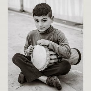 This is an action shot of a child in refugee camp playing Drums for Schools' Natural Drum