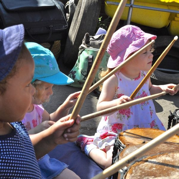 This is an action shot of three children playing Drums for Schools' Dundun Bamboo