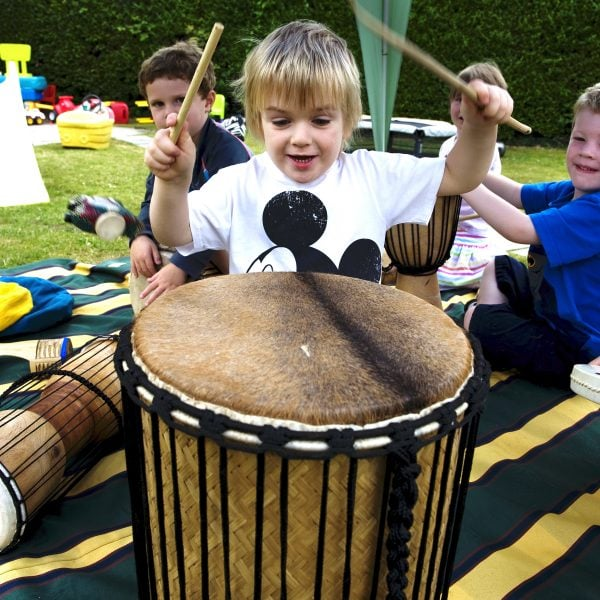This is an action shot of Early Years children playing Drums for Schools' Kenkeni Bamboo