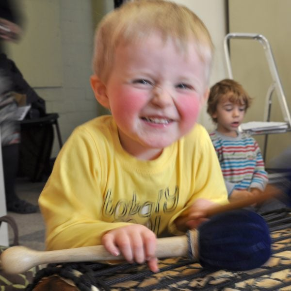 This is an action shot of an Early Years child smiling holding Drums for Schools' Dundun Bamboo beater