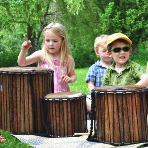 This is an action shot of Early Years children playing Drums for Schools' large set of Dundun Recycled Wood