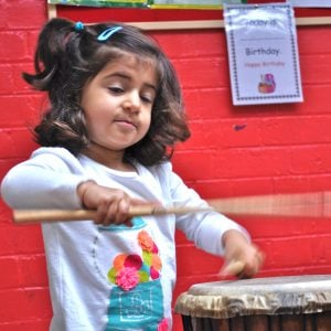 This is an action shot of an Early Years child playing Drums for Schools' Djembe Drum