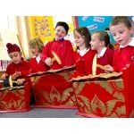 This is an action shot of primary age children playing the Drums for Schools standard gamelan