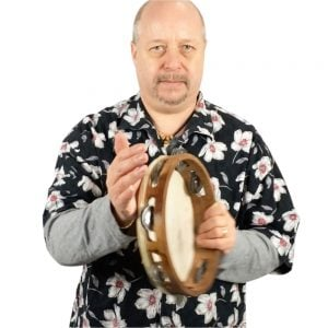 Image showing Andy Gleadhill playing tambourine, holding it vertical