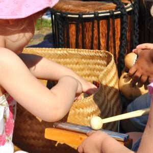 Action shot of preschool students playing Drums for Schools' basket of instruments
