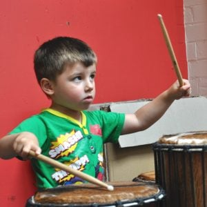 Action shot of a preschool student playing Drums for Schools' Dundun drum