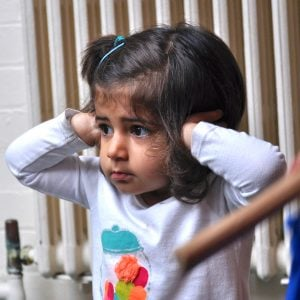 Image of a preschool student blocking her ears from loud noise