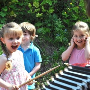 Image of one preschool student blocking her ears  besides her other friends who play drums