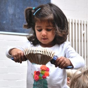 Image of an Early Years child playing Drums for Schools' Animal Clacker