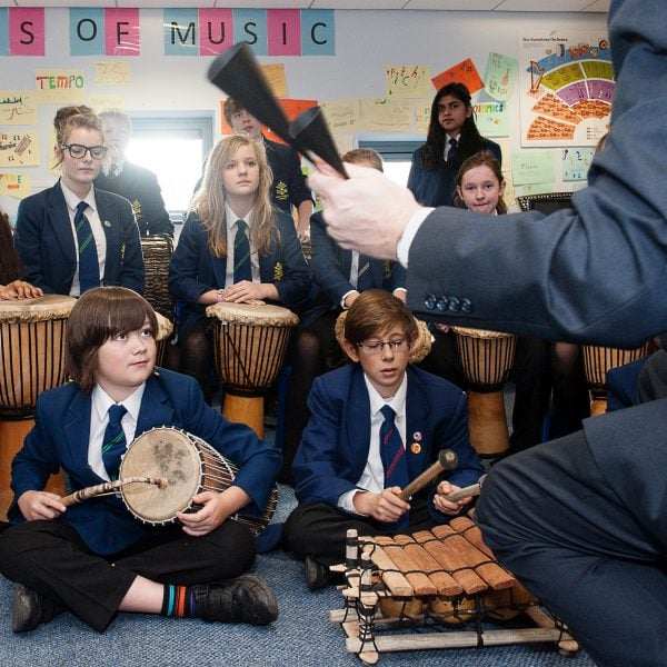 This is an action shot of some Secondary Schools children playing in a music workshop. They have a selection of West African instruments including a Talking Drum, a Balafon and Djembes. The teacher is partially in shot at the front with an Agogo.