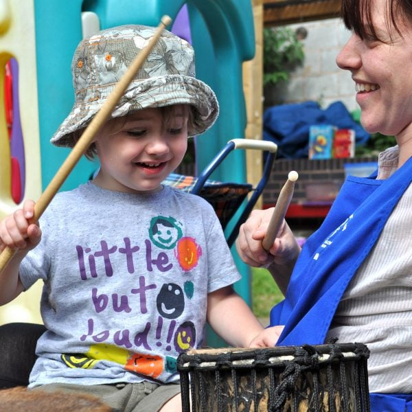 This is an action shot of an Early Years child playing Drums for Schools' Teeny Weeny Kenkeni Bamboo