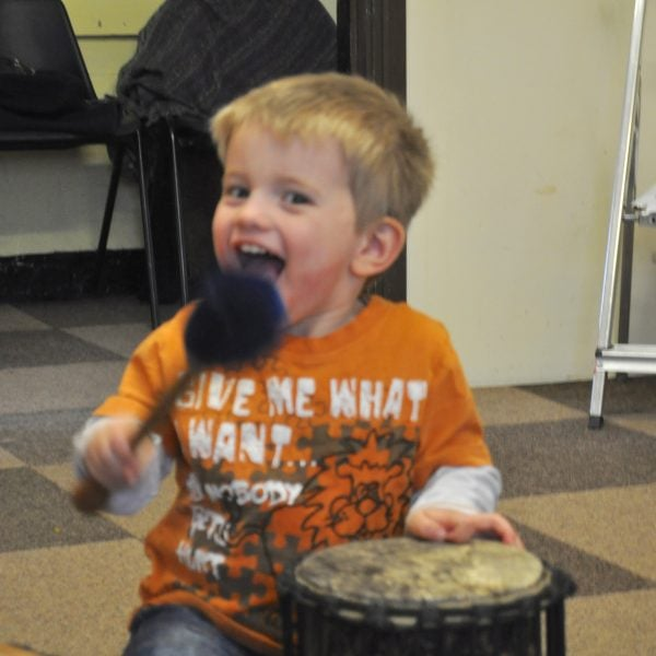 This is an action shot of an Early Years child playing Drums for Schools' Supermini Kenkeni Bamboo