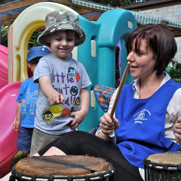 This is an action shot of Early Years children playing Drums for Schools' Mini Kenkeni Bamboo
